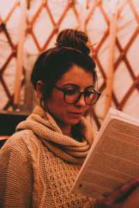 photo of woman wearing gray scarf reading book